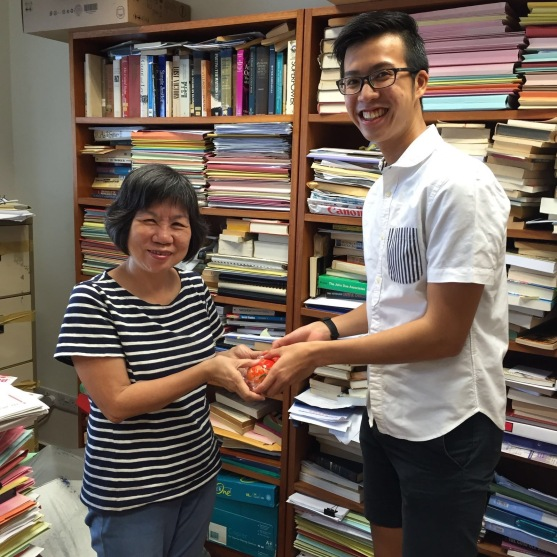HISSOC President Timotty Tay giving out mandarin oranges to Dr Quek from the History Department